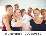 Small photo of Mixed age group of laughing women standing arm in arm taking a selfie tgether in a dance studio