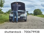 Worried man holding his head by hands standing near his old broken car with raised hood on the road                                - stock photo