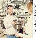 smiling man seller assisting... | Shutterstock . vector #700694362
