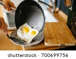 two fried eggs in a pan with... | Shutterstock . vector #700699756