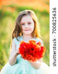 Small photo of wedding, childhood, flora concept - portrait of beautiful girl of preschool age with sly smile and flowing light brown hair, she's wearing alice blue dress and holding bright bouquet of poppies