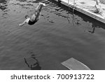 man diving into swimming pool | Shutterstock . vector #700913722