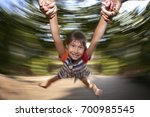 Small photo of Little girl is spinning and smiling She is happy. Father is holding her hands. Background is blurred. Long exposure was used to achieve this effect Side parts of the photo are free for text & graphics
