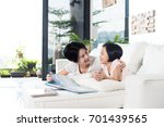 young asian mother reading a... | Shutterstock . vector #701439565
