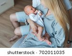 a young mother in the room... | Shutterstock . vector #702011035