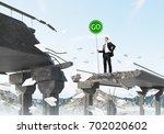 confident businessman in suit... | Shutterstock . vector #702020602