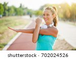 young woman is exercising on... | Shutterstock . vector #702024526