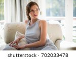 thoughtful woman sitting in... | Shutterstock . vector #702033478