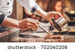 hand of man take cooking of... | Shutterstock . vector #702060208