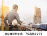 civil engineer holding helmet... | Shutterstock . vector #702069196