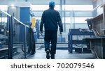 factory worker in a hard hat is ... | Shutterstock . vector #702079546