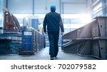 factory worker in a hard hat is ...   Shutterstock . vector #702079582