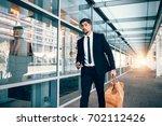 handsome business traveler... | Shutterstock . vector #702112426
