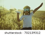 Small photo of Young Boy playing to be airplane pilot, funny guy with aviator cap and glasses, carries in his hand a plane made of paper