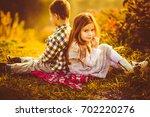children sit side by side on a...   Shutterstock . vector #702220276