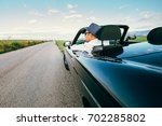 man drive cabriolet car on... | Shutterstock . vector #702285802