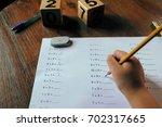 a school kid doing 1st grade... | Shutterstock . vector #702317665