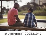 smiling father talking to son... | Shutterstock . vector #702331042