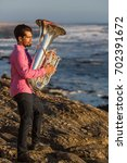 Small photo of Musician play to musical instrument Tuba on romantic sea shore.
