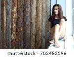 a pretty  slender brunette sits ... | Shutterstock . vector #702482596