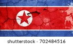 Small photo of Damaged North Korea flag painted on cracked aged city wall texture. Conceptual disintegration and poverty background.