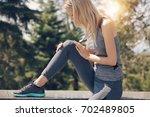 knee injury  woman runner with...   Shutterstock . vector #702489805