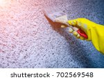 hand in glove with a paint... | Shutterstock . vector #702569548