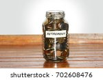 a glass jar full of coins to... | Shutterstock . vector #702608476