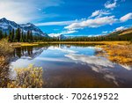 sky and clouds reflected in... | Shutterstock . vector #702619522
