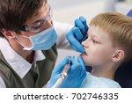male dentist examines the teeth ... | Shutterstock . vector #702746335