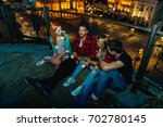 friends having fun on a rooftop ... | Shutterstock . vector #702780145