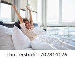 young woman stretching in bed | Shutterstock . vector #702814126