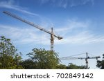 2 big cranes against blue sky | Shutterstock . vector #702849142