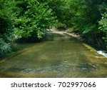 road under the water crossing... | Shutterstock . vector #702997066
