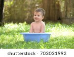 outdoor baby bathing. happy... | Shutterstock . vector #703031992