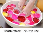 female feet in rose petals... | Shutterstock . vector #703245622