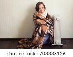 young cold woman wrapped in... | Shutterstock . vector #703333126