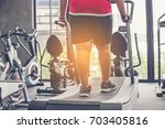 fat man walking on treadmill at ... | Shutterstock . vector #703405816