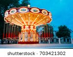 Brightly Illuminated  Empty Carousel Merry-Go-Round With Seats Suspended On Chains Without People Waiting For Its Visitors. Summer Evening In City Amusement Park.