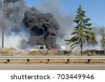 Small photo of Commercial business burns in brush fire along I-5 south of olympia, Washington. Tires and structures burn hot with flames and billowing black smoke.