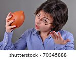 Young woman trying to get money from her piggy bank - stock photo