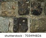 decorative stone in cement | Shutterstock . vector #703494826