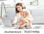 young mother holding baby while ... | Shutterstock . vector #703574986