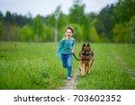 a little boy runs across the... | Shutterstock . vector #703602352