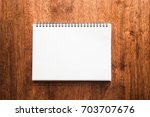 blank notepad on wooden table. | Shutterstock . vector #703707676