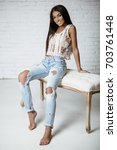 Small photo of Young beautiful showy girl with luxurious, shiny hair sitting on a bar stool. Brown hair, blue eyes, big lips. Blue ragged jeans. Fashion, beauty. Salon.