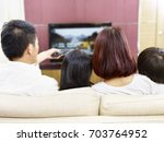 asian family sitting on couch... | Shutterstock . vector #703764952