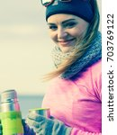 Small photo of Woman athlete fit girl wearing warm sporty clothes outdoor in cold weather drinking hot tea from vacuum flask thermos, warming up. Sports, activities, hiking in winter or autumn time