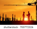Small photo of Silhouette of architect explaining the construction worker to the building plan for the correct understanding with light lens flare effect