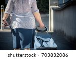 old woman walking with trolley  ... | Shutterstock . vector #703832086